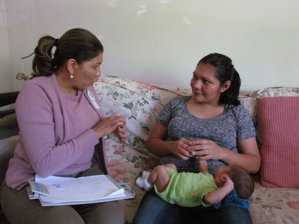 Woman talking to a mother with infant on her lap.