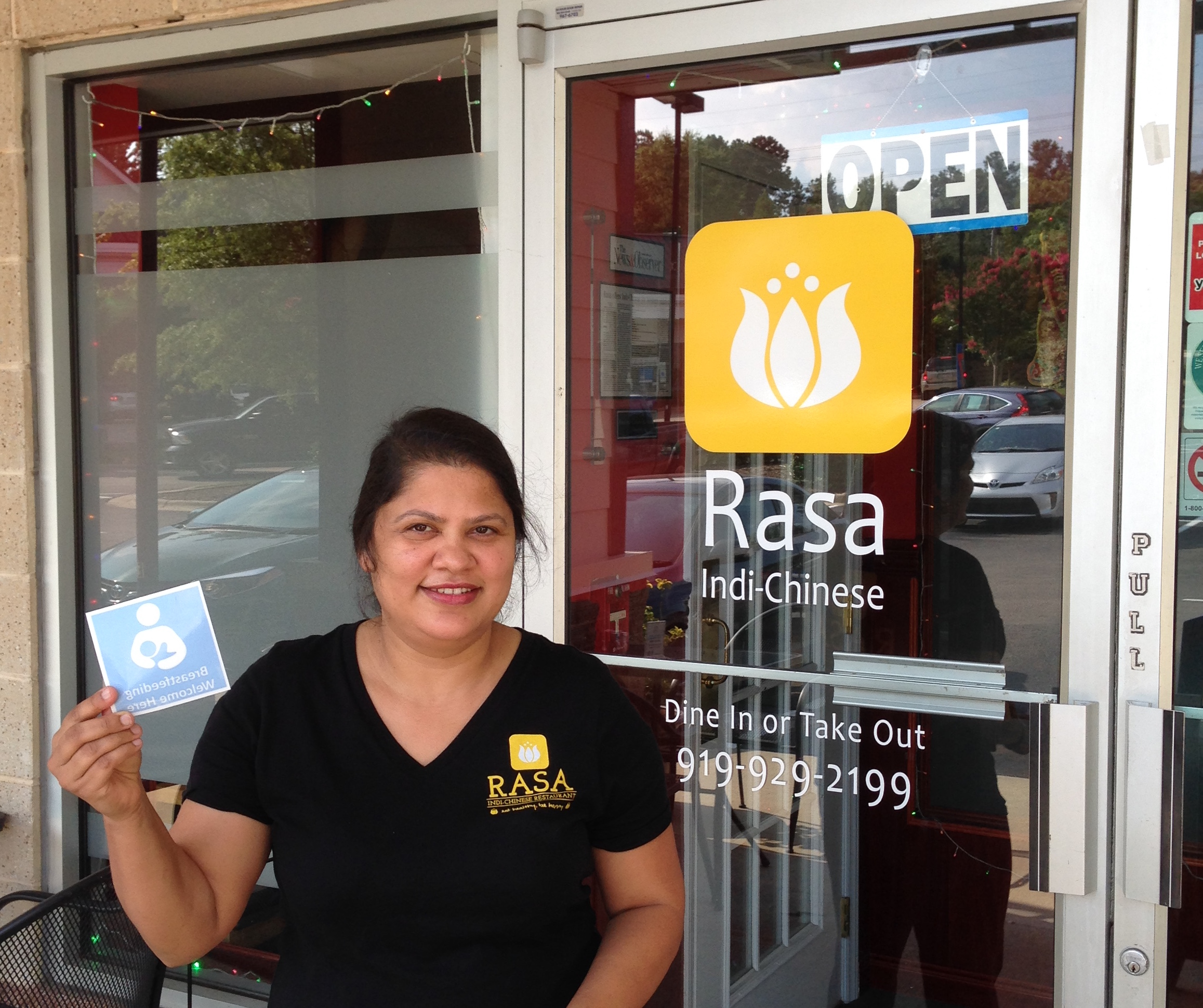 Employee of Rasa Indi-Chinese Restaurant standing in front of restaurant door holding breastfeeding communities cling