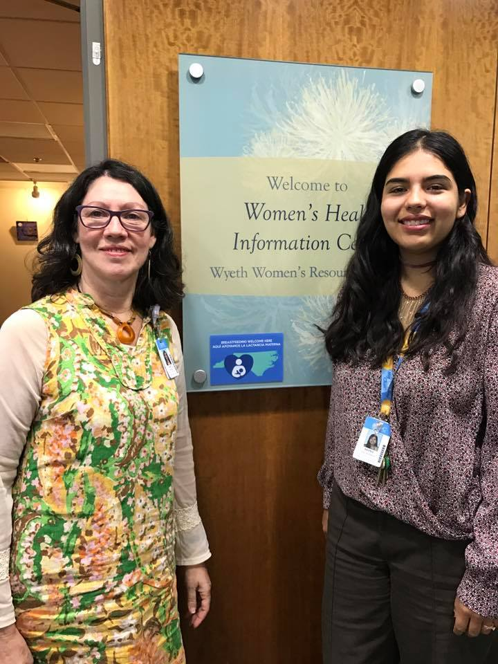 Two women are smiling and standing in front of the Women's Health Information Center