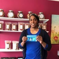 Tonya, owner of Tonya's Cookies, standing in shop and holding the breastfeeding communities cling