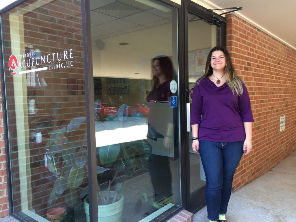 Woman is smiling and standing in front of the door to Triangle Acupuncture Clinic