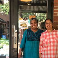 Vimala and friend are standing in front of Vimala's Curryblossom Café door