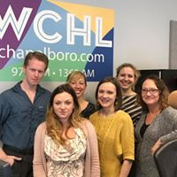 Six employees of WCHL standing in front of the WCHL chapelboro.com sign