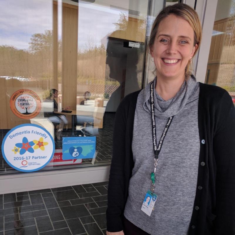 Front door of Chapel Hill Library with employee standing in front of the door