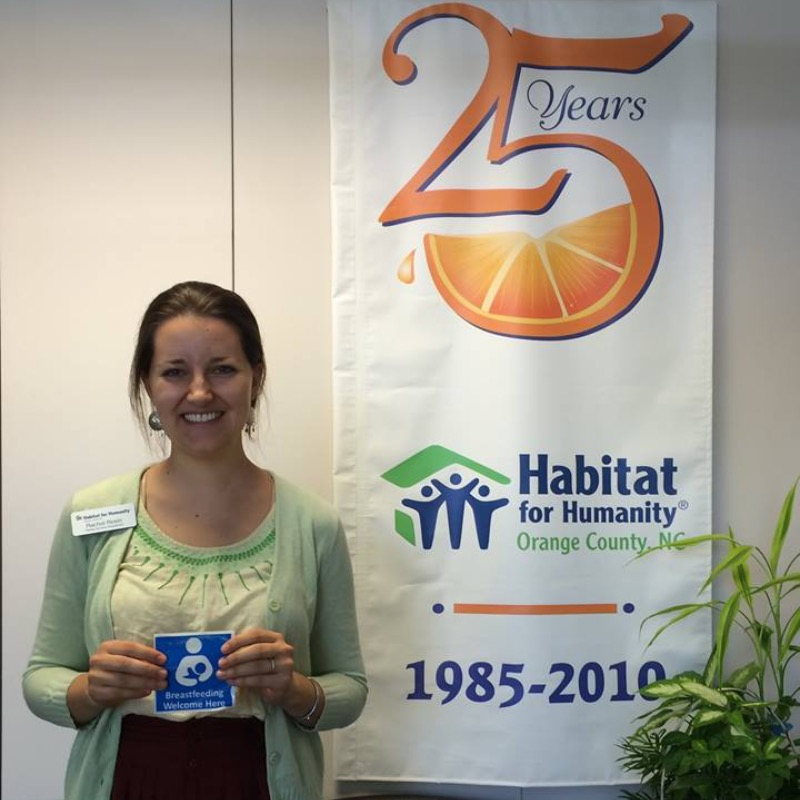 Habitat for Humanity of Orange County employee standing in front of 25 years banner