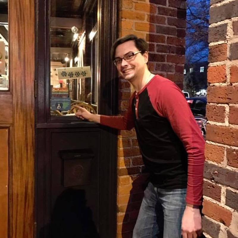 Spotted Dog Restaurant employee standing in front of restaurant door pointing to breastfeeding communities cling on the door