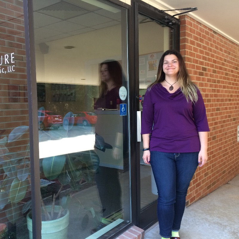 Triangle Acupuncture Clinic employee standing in front of office door