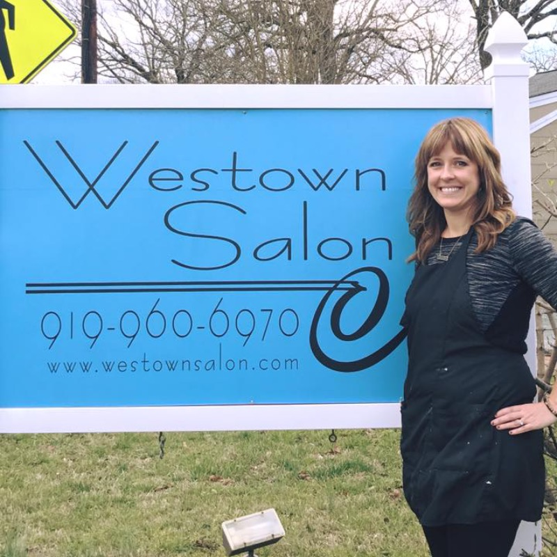 Employee of Westown Salon standing in front of the outdoor store sign
